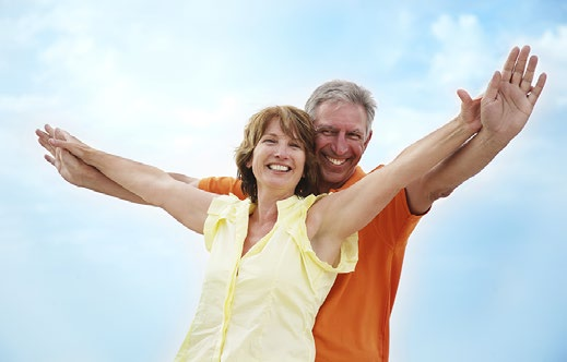 Man and woman with arms outstretched carefree
